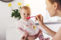 En kvinna matar en behandla som ett barn med en sked Ett barn sitter på en tabell i köket och äter med nöje Royaltyfri Fotografi