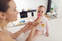 En kvinna matar en behandla som ett barn med en sked Ett barn sitter på en tabell i köket och äter med nöje Fotografering för Bildbyråer