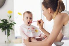 En kvinna matar en behandla som ett barn med en sked Ett barn sitter på en tabell i köket och äter med nöje Arkivfoto