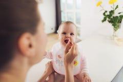 En kvinna matar en behandla som ett barn med en sked Ett barn sitter på en tabell i köket och äter med nöje Royaltyfria Foton