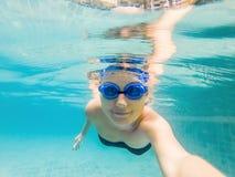 En kvinna med att dyka exponeringsglas simmar i pölen under vattnet arkivbild