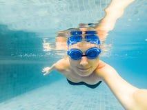 En kvinna med att dyka exponeringsglas simmar i pölen under vattnet arkivbilder