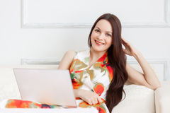 En kvinna med bärbara datorn är på soffan Arkivbild