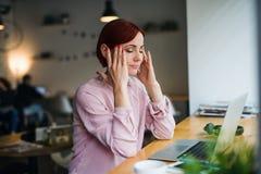 En kvinna med bärbara datorn som sitter på tabellen i ett kafé som lider från huvudvärk royaltyfri foto
