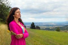En kvinna med en blomma i hennes hand Fotografering för Bildbyråer