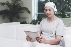 En kvinna med cancer sitter på en vit soffa i en modern klinik Hon har ett rosa band på hennes skjorta Arkivfoto