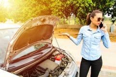 En kvinna med en bruten bil som talar på telefonen, och väntar på hjälp Arkivfoton