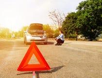 En kvinna med en bruten bil, väntar på hjälp Royaltyfri Bild