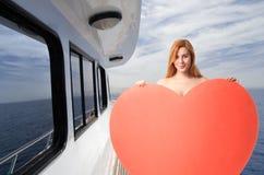En kvinna med en hjärta på en yacht arkivfoton