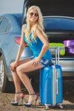 En kvinna med en resväska nära bilen Arkivbild