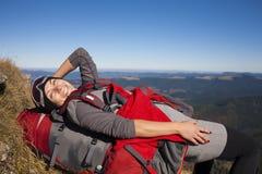En kvinna med en ryggsäck som vilar på en vagga arkivfoto