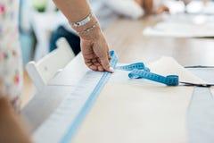 En kvinna med ett armband mäter tyg Mode skräddares seminarium royaltyfri fotografi