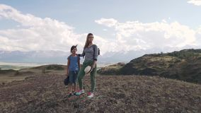 En kvinna med ett barn som beundrar sikten av bergen familj av turister med ryggsäckar mamman och den lilla dottern gick stock video