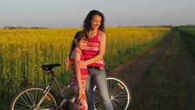 En kvinna med ett barn som håller ögonen på solnedgången En sportfamilj med en cykel Momen kramar henne dottern lager videofilmer