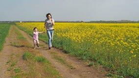 En kvinna med ett barn spelar i natur En lycklig familj kör i den nya luften En flicka med ett barn kör längs en landsro lager videofilmer
