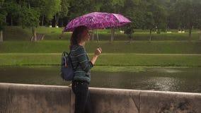 En kvinna med ett paraply i natur i sommarregnet Royaltyfri Fotografi