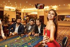 En kvinna med exponeringsglas av champagne i en klänning på tabellrouletten i kasino arkivbild