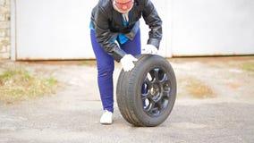 En kvinna med exponeringsglas rullar ett bilgummihjul med en diskett över asfalten stock video