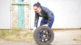 En kvinna med exponeringsglas rullar ett bilgummihjul med en diskett ?ver asfalten stock video