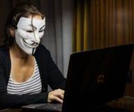 En kvinna med fejdmaskeringen framme av en bärbar dator royaltyfri foto