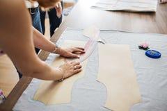 En kvinna med härliga cirklar och armband arbetar med en sy linjal Fasion skräddares seminarium royaltyfria bilder
