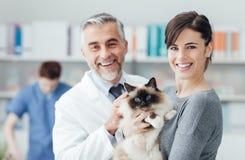En kvinna med hennes katt på den veterinär- kliniken Arkivfoto