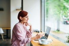 En kvinna med kaffe och telefonen som sitter på tabellen i ett kafé royaltyfri foto