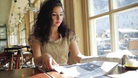 En kvinna med lockigt hår sitter nära ett fönster i ett kafé och läser enhaired kvinna sitter nära ett fönster i ett kafé och ett lager videofilmer