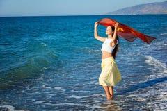 En kvinna med pareoen är på en segla utmed kusten Arkivbild