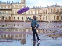 En kvinna med en ryggsäck och ett paraply i ett härligt historiskt ställe på bakgrunden av en forntida slott Gatchina arkivfoton