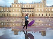 En kvinna med en ryggsäck och ett paraply i ett härligt historiskt ställe på bakgrunden av en forntida slott Gatchina royaltyfria foton