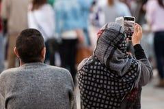 En kvinna med en sjalett att ta bilder av processionen med hennes mobiltelefon arkivfoton