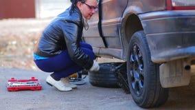 En kvinna med en st?lar f?ller ned baksidan av bilen till jordningen arkivfilmer