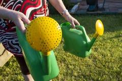 En kvinna med två bevattna cans går till trädgården Fotografering för Bildbyråer