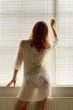 En kvinna nära fönstret hemma arkivfoto