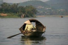 En kvinna navigerar med ett fartyg på en flod (Vietnam) Arkivbild