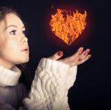 En kvinna och en brännhet hjärta. Arkivbild