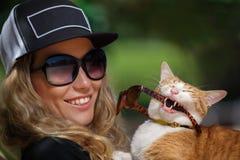 En kvinna och en katt är nära den utomhus- simbassängen royaltyfri bild