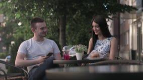 En kvinna och en man har en konversation i ett sommarkafé stock video