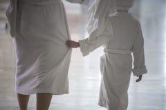 En kvinna och ett barn går i vita badrockar fotografering för bildbyråer