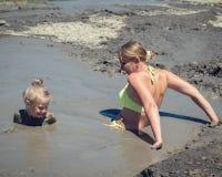 En kvinna och hennes dotter simmar i en gyttjavulkan på en sommarmorgon Royaltyfri Fotografi