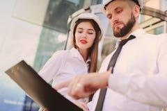 En kvinna och en man i affärskläder och i vita konstruktionshjälmar diskuterar ett konstruktionsplan eller ett avtal Royaltyfria Bilder