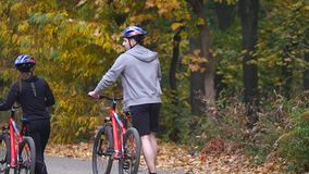 En kvinna och en man som rider en cykel om höstdagen stock video