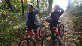 En kvinna och en man som rider en cykel om höstdagen lager videofilmer