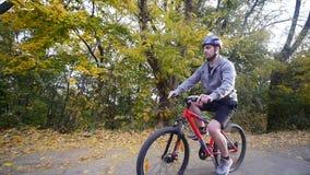 En kvinna och en man som rider en cykel om höstdagen långsam rörelse lager videofilmer