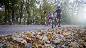 En kvinna och en man som rider en cykel om höstdagen Vektorillustration för din design långsam rörelse stock video
