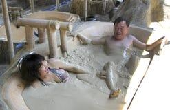 En kvinna och en man tar ett gyttjebad på I - tillgripa, Nha Trang, Vietnam Arkivfoto