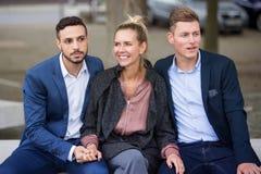 En kvinna och två män som tillsammans sitter på bänk Royaltyfri Foto