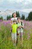 En kvinna och två pojkar står på fält av mjölkörten Royaltyfri Fotografi