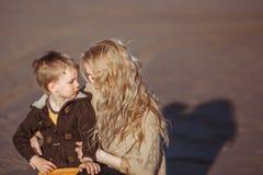En kvinna omfamnar hennes son, som ser henne Arkivfoto